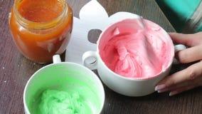 Vrouw die room voor het maken van cakes voorbereiden Van het mengelingenroomkaas en voedsel kleuring Dichtbij is een kruik jam stock footage