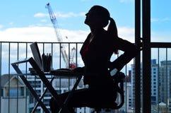 Vrouw die rugpijn hebben terwijl het werken bij bureau Stock Afbeelding