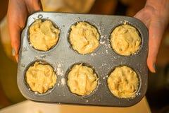 Vrouw die ruwe muffins in muffinvorm houden royalty-vrije stock foto