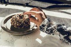 Vrouw ` die s een chocoladedoughnut met de hand plukken Royalty-vrije Stock Foto