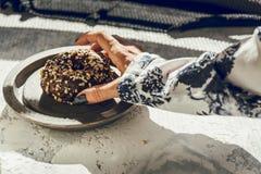 Vrouw ` die s een chocoladedoughnut met de hand plukken Royalty-vrije Stock Afbeelding