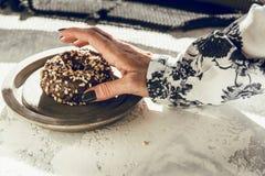 Vrouw ` die s een chocoladedoughnut met de hand plukken Stock Foto