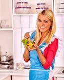 Vrouw die salade eet bij keuken Stock Foto's