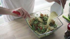 Vrouw die salade mengen met houten lepel en de langzame motie van kouskouskasha toevoegen stock video