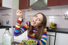 Vrouw die salade op de keuken eet Stock Foto's