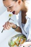Vrouw die salade thuis eten stock foto
