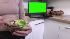 Vrouw die salades in kom mengen dicht omhoog dichtbij laptop PC met het groene scherm stock footage