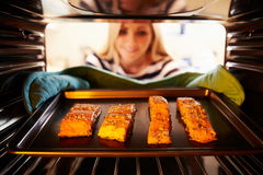 Vrouw die Salmon Fillets Into Oven To Cook zetten royalty-vrije stock foto