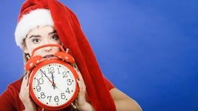 Vrouw die Santa Claus-de klok van de kostuumholding dragen Stock Afbeelding