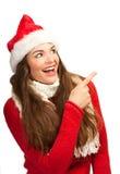 Vrouw die in santahoed aan copyspace richt Stock Afbeeldingen