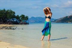 Vrouw die sarongen op tropisch strand dragen Stock Afbeeldingen