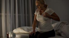 Vrouw die scherpe pijn in haar borst voelen, die aan hartaanval lijden bij nacht, gezondheid stock afbeeldingen