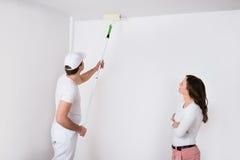 Vrouw die Schilder Painting On Wall bekijken stock afbeeldingen