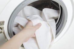 Vrouw die schone witte handdoeken na was krijgen Wasmachine met kleren stock fotografie