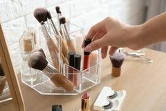 Vrouw die schoonheidsmiddelen van organisator voor make-upproducten nemen stock foto