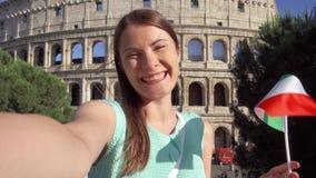 Vrouw die selfie dichtbij Colosseum in Rome, Italië doen Tiener die Italiaanse vlag in langzame motie golven stock footage