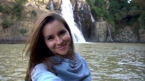 Vrouw die selfie dichtbij waterval in Dalat, Vietnam nemen stock videobeelden