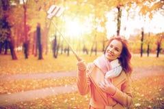 Vrouw die selfie door smartphone in de herfstpark nemen Stock Afbeelding