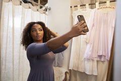 Vrouw die selfie in een boutique kleedkamer nemen royalty-vrije stock fotografie