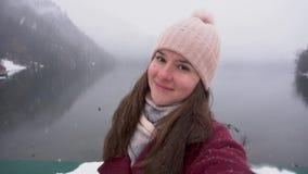 Vrouw die selfie en bij Ritsa-meer in Abchazië glimlachen nemen Sneeuwdag in de winter stock videobeelden