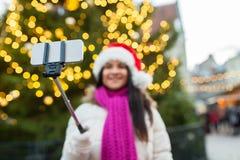 Vrouw die selfie met smartphone bij Kerstmis nemen Stock Foto's