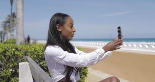 Vrouw die selfie op bank nemen stock videobeelden