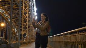 Vrouw die selfie op mobiele telefoon in St. Petersburg, brug bij nacht maken stock videobeelden