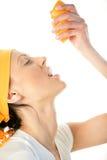Vrouw die sinaasappel drukt in mond Royalty-vrije Stock Afbeeldingen
