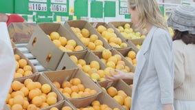 Vrouw die sinaasappel kiezen bij de supermarkt van de fruitgroente stock videobeelden