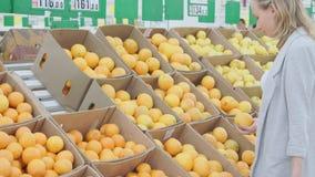 Vrouw die sinaasappel kiezen bij de supermarkt van de fruitgroente stock video