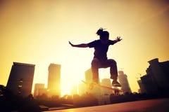 Vrouw die skateboarder bij zonsopgangstad met een skateboard rijden stock fotografie