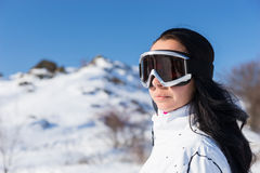 Vrouw die Ski Goggles op Sneeuw Behandelde Berg dragen stock fotografie