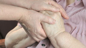 Vrouw die slappe gerimpelde handen van oude vrouw houden stock footage