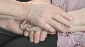 Vrouw die slappe gerimpelde handen van oude vrouw houden stock video
