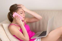 Vrouw die slecht nieuws op cellphone thuis horen royalty-vrije stock fotografie