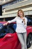 Vrouw die sleutel van nieuwe rode sportwagen toont Royalty-vrije Stock Fotografie