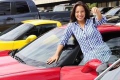 Vrouw die sleutel van nieuwe sportwagen toont Stock Afbeeldingen