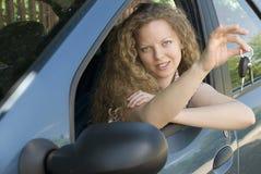 Vrouw die sleutels aanbiedt aan haar nieuwe auto Stock Afbeeldingen
