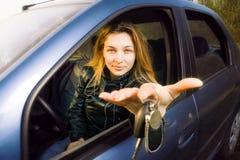 Vrouw die sleutels aanbiedt aan nieuwe auto Royalty-vrije Stock Foto's