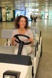 Vrouw die in slijtage op elektrische auto berijdt Stock Foto's