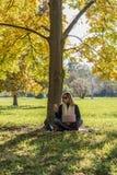 Vrouw die slimme telefoon en laptop met behulp van onder kleurrijke dalingsboom Stock Fotografie