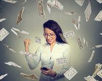 Vrouw die slimme telefoon met behulp van die online zaken bouwen gelddollars maken die neer vallend Stock Foto's