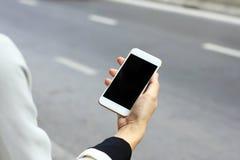 Vrouw die slimme telefoon met behulp van door de straat, die de toepassing van de taxidienst gebruiken stock foto