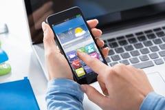 Vrouw die Slimme Telefoon met Toepassingen op het Scherm met behulp van stock afbeelding