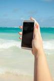 Vrouw die slimme telefoon voor het nemen van foto op een strand met behulp van Royalty-vrije Stock Fotografie