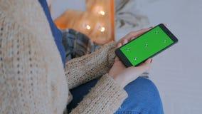Vrouw die slimme telefoontelefoon bekijken met het groene scherm stock videobeelden