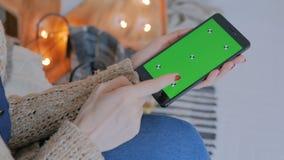 Vrouw die slimme telefoontelefoon met het groene scherm met behulp van stock videobeelden