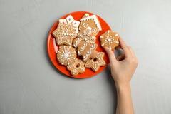 Vrouw die smakelijk eigengemaakt Kerstmiskoekje van plaat nemen Royalty-vrije Stock Fotografie
