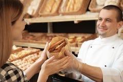 Vrouw die smakelijk gebakje in bakkerij kopen stock foto