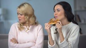 Vrouw die smakelijke pizza eten terwijl vriend het vechten met snel voedsel die wens eten stock videobeelden